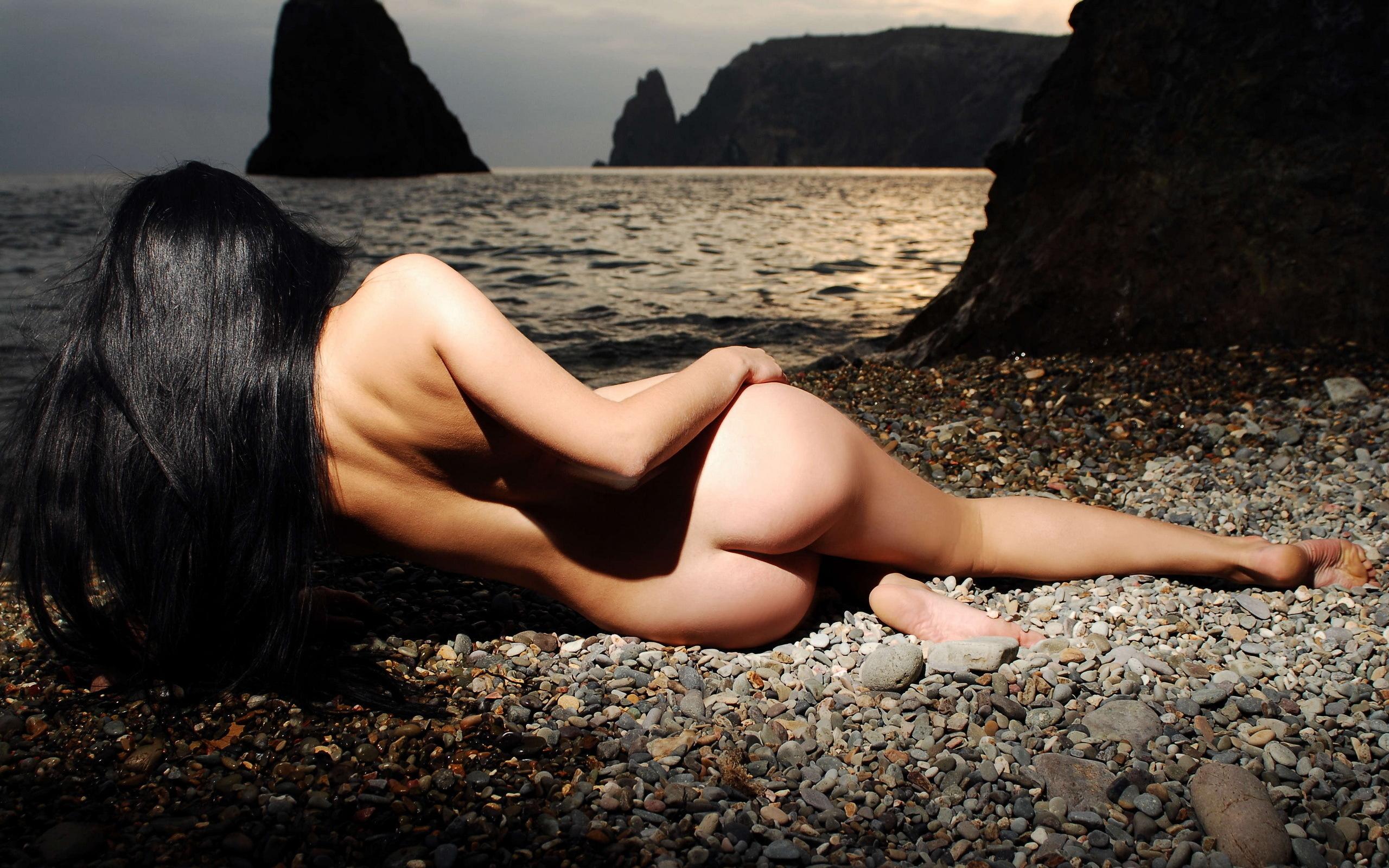 Грудастая модель позирует голой на берегу моря  499587