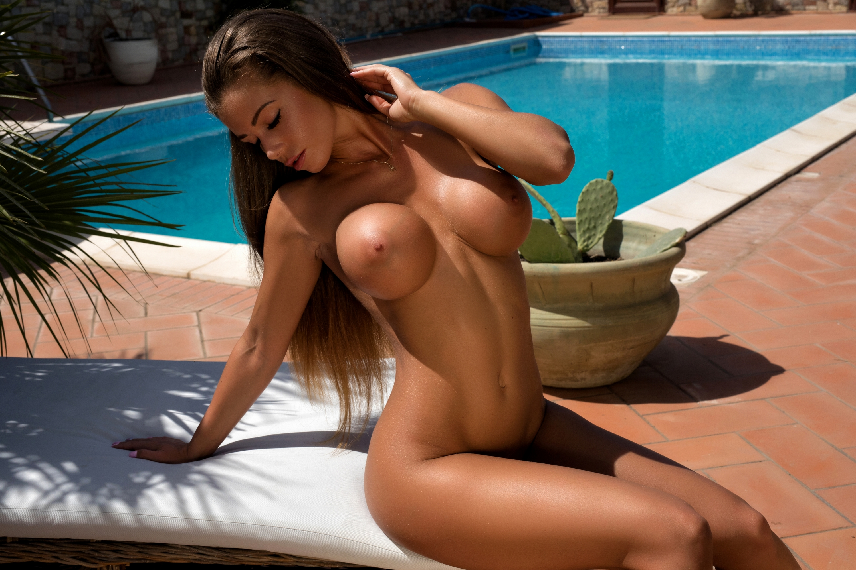 Tanned webcam babe plays with her amazing fake tits